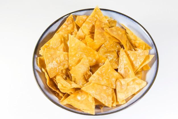 Chips de nachos dans le bol bleu sur fond blanc, snack