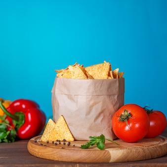 Chips de nachos dans le paquet avec persil et tomate