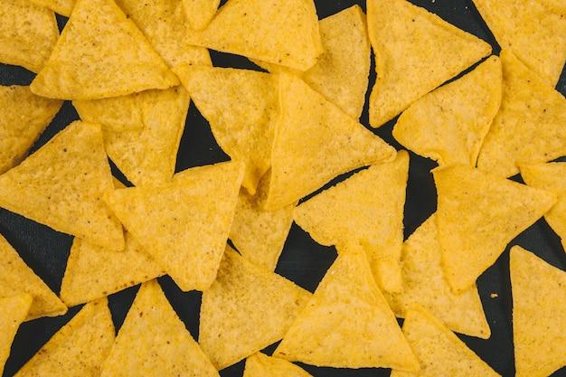 Chips de nachos mexicains jaunes sur fond noir