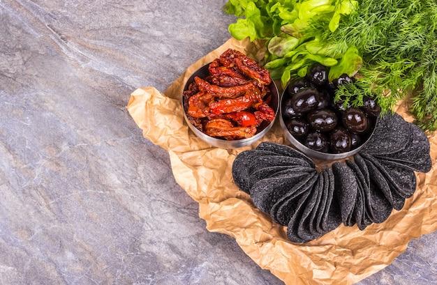 Chips noirs aux olives et tomates