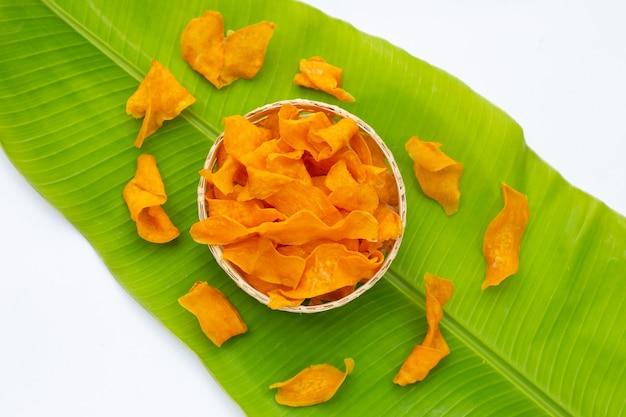 Chips de patate douce dans un panier de bambou sur feuille de bananier