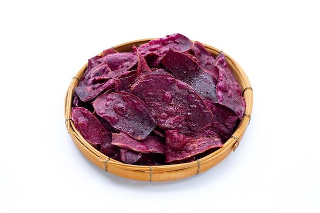 Chips de patates douces violettes dans un panier en bambou sur une surface blanche.