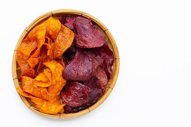 Chips de patates douces violettes et jaunes dans un panier en bambou sur fond blanc.