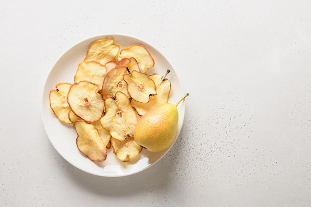 Chips de poire aux fruits sur fond blanc. dessert végétalien sans sucre.