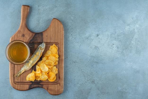 Chips, poisson et verre de bière sur une planche, sur le fond de marbre.