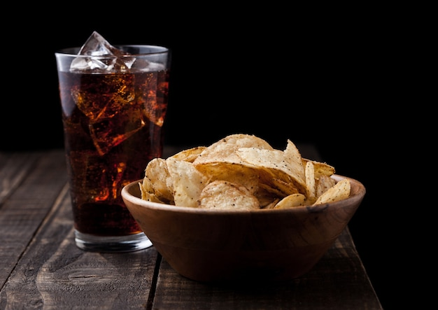 Chips de poivre croustillant dans un bol en bois avec du cola soda sur fond de bois