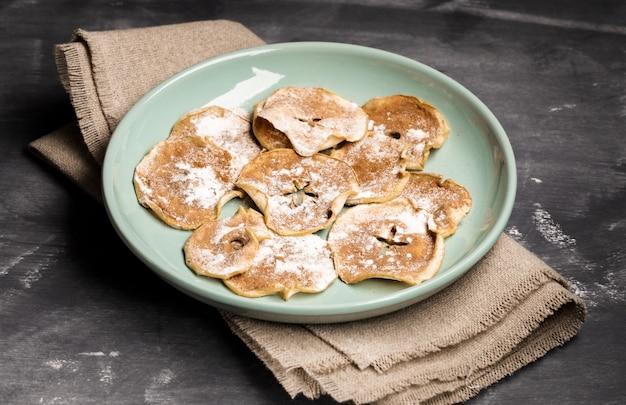Chips de pomme saupoudrés de sucre en poudre et de cannelle sur plaque verte sur toile de jute
