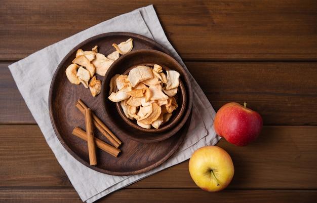 Chips de pommes maison sucrées cuites à la cannelle dans un bol en bois sur fond de bois. produit végétalien et diététique
