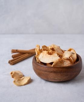 Chips de pommes maison sucrées cuites à la cannelle dans un bol en bois sur fond gris. produit végétalien et diététique