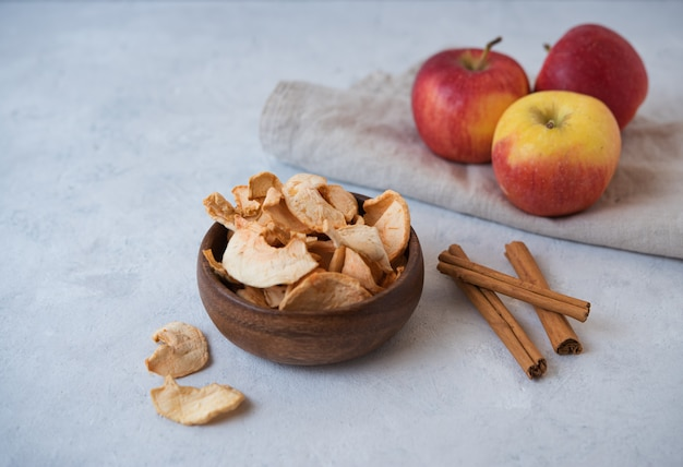 Chips de pommes maison sucrées cuites à la cannelle dans un bol en bois sur fond gris