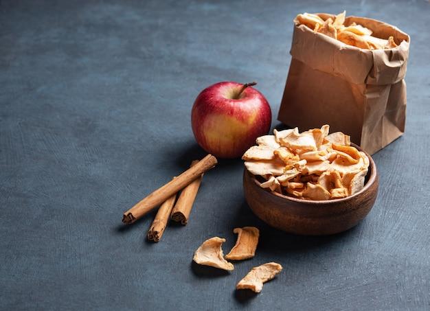 Chips de pommes maison sucrées séchées à la cannelle dans un bol en bois sur fond bleu foncé