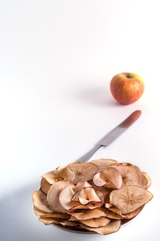 Chips de pommes séchées dans une assiette au premier plan et pomme fraîche