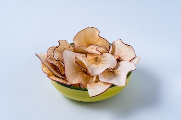 Chips de pommes séchées dans un bol au-dessus d'une table bleu clair.