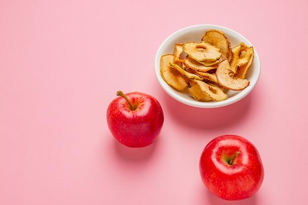 Chips de pommes séchées dans un bol en céramique avec des pommes rouges fraîches sur la table