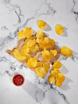 Chips de pommes de terre et ketchup sur une table en marbre - mise à plat