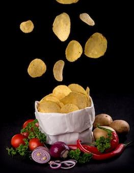 Chips de pommes de terre sur une planche en bois sombre. fast food. fond sombre.