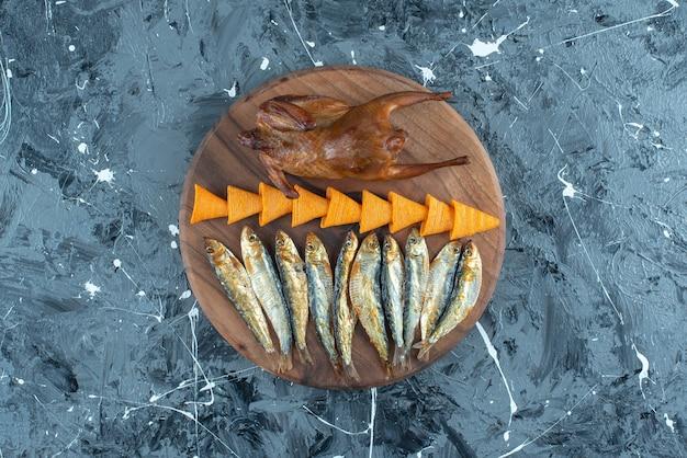 Chips, poulet grillé et poisson à bord sur marbre.