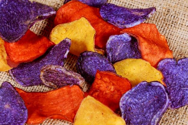 Chips salés de betterave et de carotte dans une vieille assiette bleue.