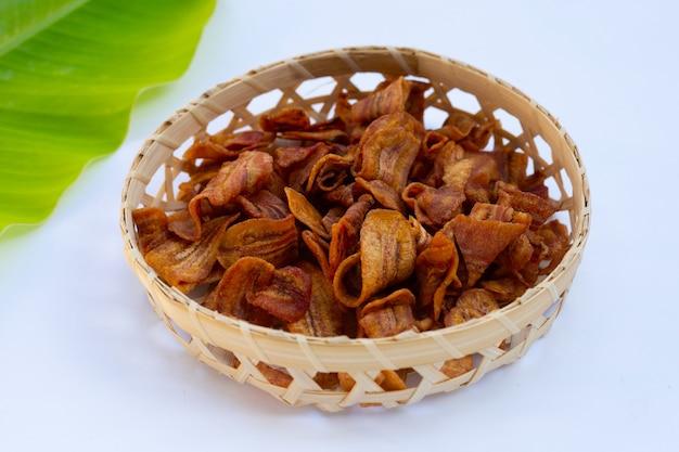 Chips de tranche de banane dans un panier en bambou sur fond blanc.