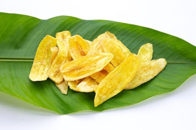 Chips de tranche de banane sur des feuilles vertes sur fond blanc.