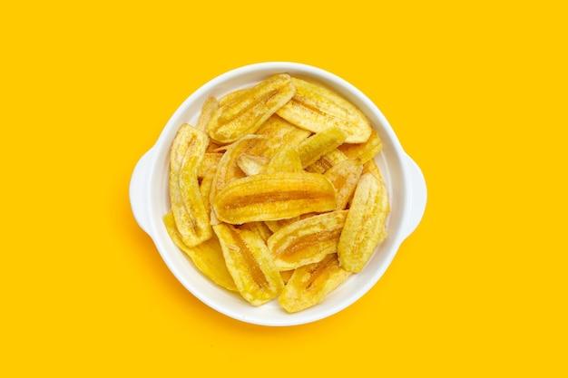 Chips de tranche de banane en plaque blanche sur fond jaune.
