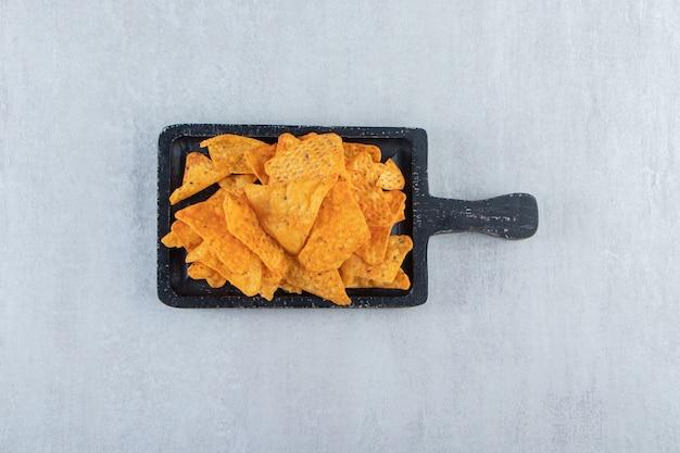 Chips de triangle épicé sur une planche à découper noire sur pierre.