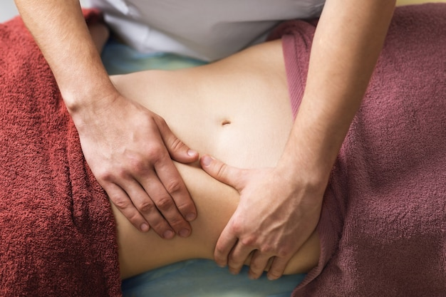 Le chiropraticien effectue un massage sur l'abdomen