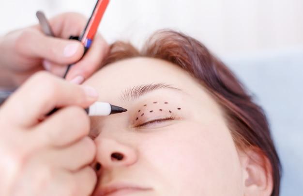 Chirurgien corrigeant le visage féminin avant l'opération