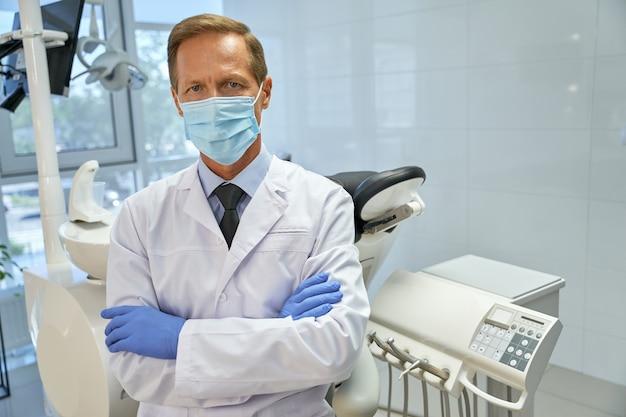Chirurgien-dentiste professionnel en masque posant dans sa clinique