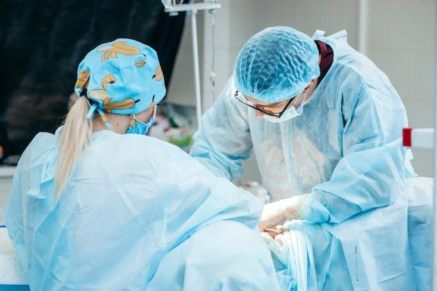 Chirurgien effectuant une intervention chirurgicale sur les seins dans la salle d'opération de l'hôpital. chirurgien en masque portant des loupes chirurgicales pendant une procédure médicale.
