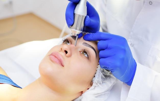 Le chirurgien esthéticienne enlève la pigmentation et les filets vasculaires sur la peau du patient