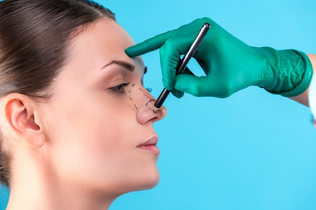 Chirurgien esthétique examinant une cliente au bureau. le médecin trace des lignes avec un marqueur, la paupière avant la chirurgie plastique, la blépharoplastie. chirurgien ou esthéticienne mains touchant le visage de la femme. rhinoplastie