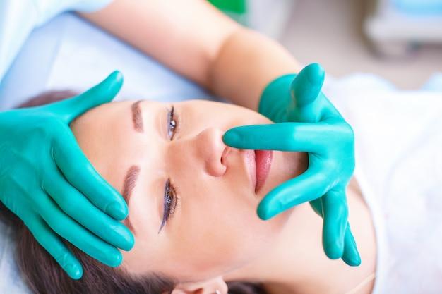Chirurgien esthétique examinant une cliente en clinique avant plast