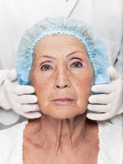 Chirurgien faisant une vérification de la peau d'une femme d'âge moyen avant une chirurgie plastique