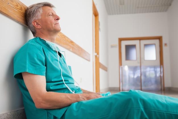 Chirurgien fatigué est assis sur le sol dans le couloir de l'hôpital