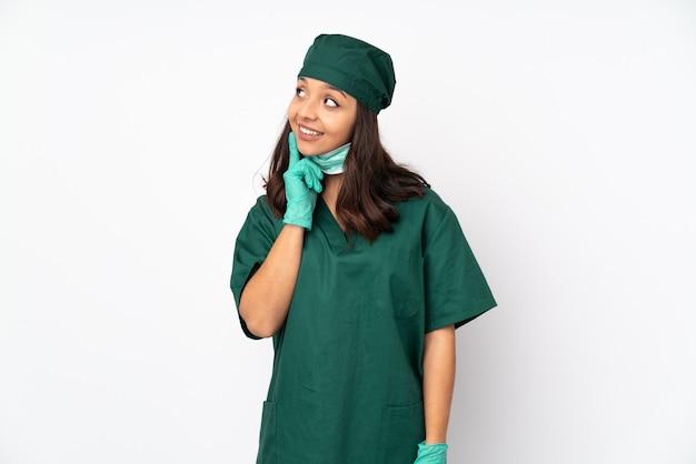 Chirurgien femme en uniforme vert sur blanc en pensant à une idée tout en levant