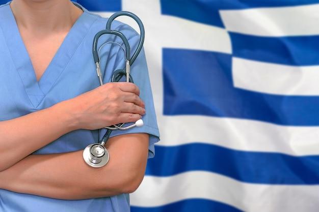 Chirurgien ou médecin avec stéthoscope sur le drapeau de la grèce. soins de santé, chirurgie et concept médical en grèce