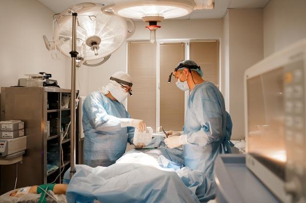 Le chirurgien ouvre la boîte et prend un implant en silicone. opération plastique d'augmentation thoracique dans une clinique médicale. le chirurgien insère un implant en silicone dans la poitrine de la femme.