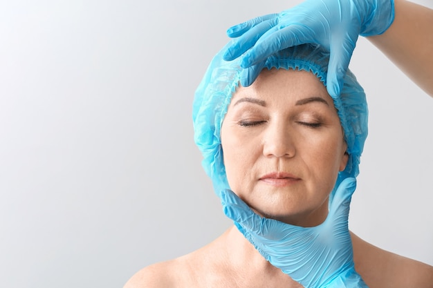 Chirurgien plasticien touchant le visage d'une femme mûre sur fond gris