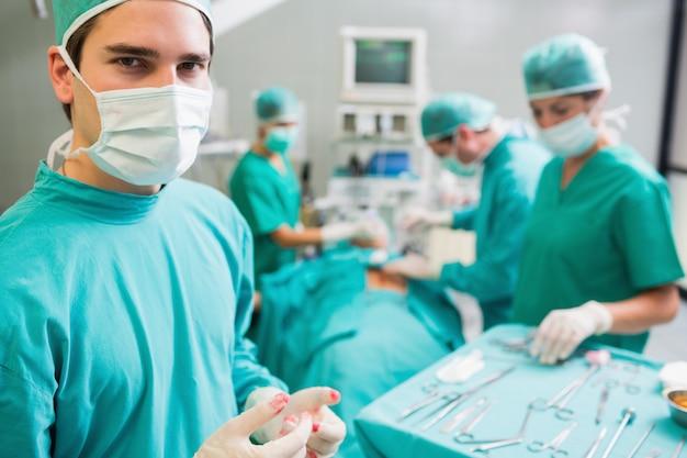Chirurgien portant des gants sanglants en regardant la caméra