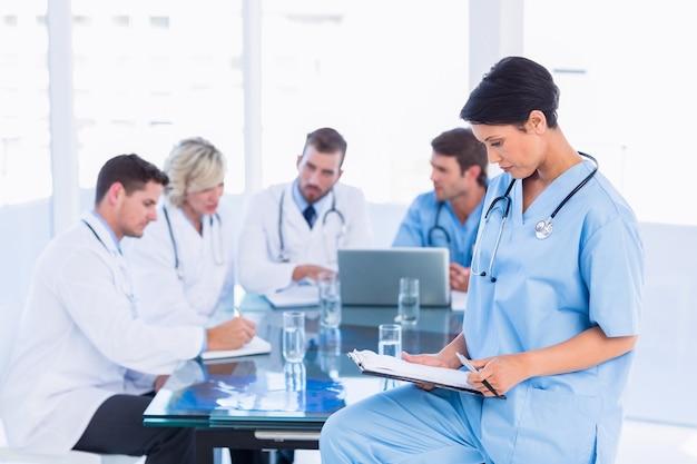 Chirurgien regardant des rapports avec des collègues en réunion