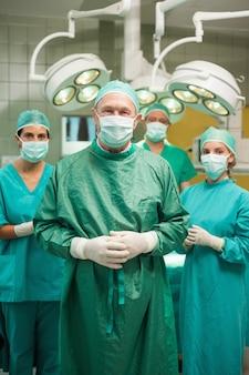 Chirurgien souriant posant avec une équipe médicale