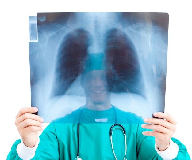 Chirurgien souriant, regardant les rayons x dans son bureau
