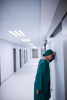 Chirurgien tendu s'appuyant sur le mur dans le couloir