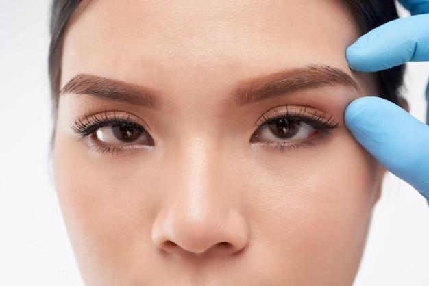 Chirurgien touchant la zone des sourcils