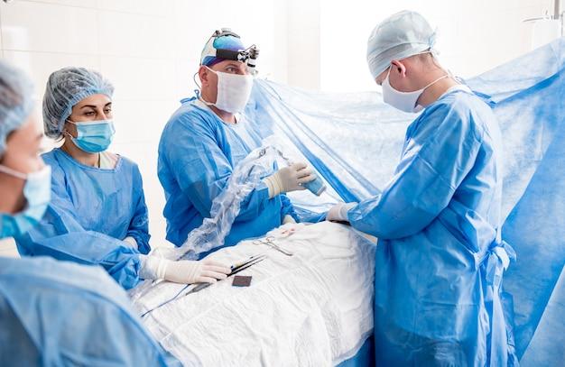 Le chirurgien utilise un appareil d'imagerie par fluorescence portable pendant le retrait du sein.