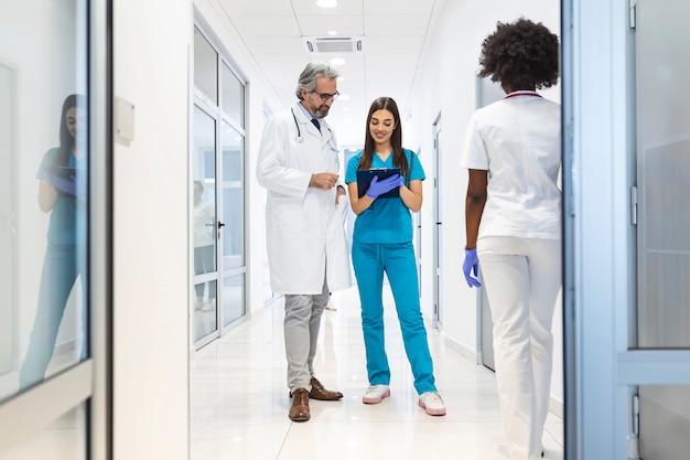 Une chirurgienne et un médecin marchent dans le couloir de l'hôpital