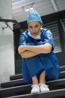 Chirurgienne réfléchie assise sur l'escalier