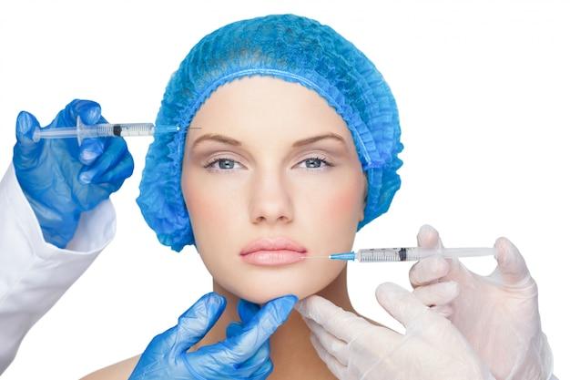 Des chirurgiens faisant une injection sur une blonde calme portant un bonnet chirurgical bleu