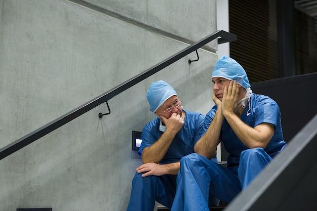 Chirurgiens masculins inquiets assis sur l'escalier